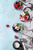 Summer dessert Eton Mess. Traditional summer dessert Eton Mess. Broken meringue with whipped cream, berry jam, fresh blueberries and raspberries in two glasses Royalty Free Stock Photo
