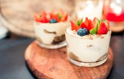 Summer dessert tiramisu, classic cheesecake with berries decorated with mint leaves. stock image