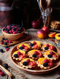 Summer dessert with various fruits. Fresh berry tartlet or cake with vanilla custard, raspberry, peach and blackberry Royalty Free Stock Photo