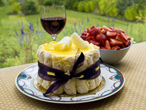Summer dessert with wine. Lemon charlotte cake with glass of wine and a bowl of strawberry set on a table overlooking garden Stock Images