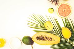 Summer diet, fresh fruits. Cuted fresh fruits with green tropical leaves flat lay pattern, summer healthy diet background, toned stock photography