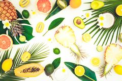 Summer diet, fresh fruits. Cuted fresh tropical fruits with green tropical leves flat lay top view pattern, summer healthy diet background, toned stock photography