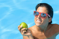 Summer diet temptation woman. Woman holding apple in resort swimming pool on summer. Diet and temptation on holidays concept with caucasian brunette model stock images