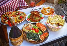 A summer  dinner .Pasta , pizza  and homemade food arrangement. In a restaurant  Rome   .Tasty and authentic Italian food Stock Images