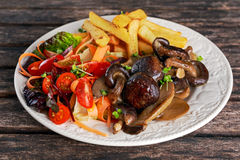 Summer dish with fried chips, red cherry tomatoe salad and grilled wild mushrooms Stock Image