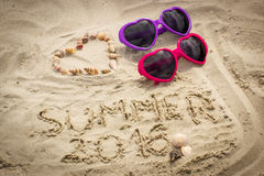 Summer 2016 drawn on sand and heart of shells with sunglasses Royalty Free Stock Images