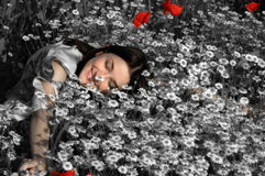 Summer Dream. Beautiful girl dreaming in a field of puppies and daisies with effect of desaturared colours to enhance the dreaming effect stock photo