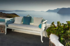 Summer dream, Santorini. Sofa with pillows and flora located on the magical terraces. Soothing view on sea level and islets. Greece royalty free stock image