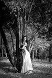 Summer dreaming. Beautiful brunette woman in black top and long white skirt standing near a cedar tree, dreaming and looking into the distance Royalty Free Stock Image