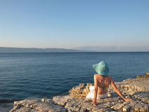 Summer dreaming. Woman taking in the beauty of the view. She is wearing linen pants and straw hat. Adriatic islands, Croatia royalty free stock photos