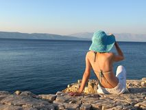 Summer dreaming. Woman wearing linen pants and straw hat. Adriatic islands, Croatia royalty free stock photography
