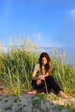 Leisure time. Young romantic girl writing with a  tall grass, sitting on sand dune at sunset time Stock Photo