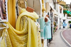Summer dresses and yellow linen scarf as a store display in the. Positano, Salerno Province, Italy - Europe. March 31, 2018.  Summer dresses and yellow linen Royalty Free Stock Images