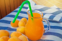 Summer drink-apricot juice in a glass jug with straw and fruit on a striped napkin on a Sunny summer day. Fresh, cup, table, background, closeup, dessert, food royalty free stock image