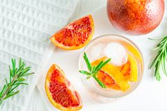 Summer drink with blood orange and rosemary on white wooden background. Flat-lay, top view royalty free stock images