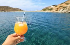 Summer drink cocktail of fresh orange juice with ice in the woman hand on the seascape background of Kolona beach Kythnos island C. Yclades Greece. Horizontal stock photography