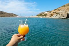 Summer drink cocktail of fresh orange juice with ice in the woman hand on the seascape background of Kolona beach. Kythnos island Cyclades Greece. Horizontal royalty free stock photography