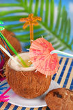 Summer drink in coconut shell. Summer fruit drink served in coconut shell on the beach royalty free stock image