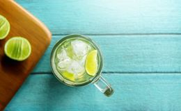 Summer Drink Concept, Glass of Caipirinha or Tropical Lemon Juic. E with Ice. Lay on Bright Blue Wooden Table. Top View Stock Photos
