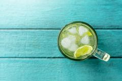Summer Drink Concept, Glass of Caipirinha or Tropical Lemon Juic. E with Ice. Lay on Bright Blue Wooden Table. Top View Royalty Free Stock Photos