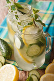 Summer drink with cucumber, lemon, ice and mint close up in a gl Stock Images