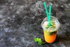Summer drink lemonade with orange and mint in the plastic cup on a dark background royalty free stock photo