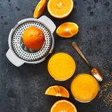 Top view of fresh orange juice in tall glass and citrus squeezer on dark concrete background royalty free stock images