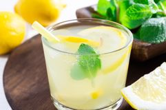 Summer drink of lemon and mint, or lemonade, on dark wooden table royalty free stock photography