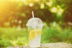 Summer Drink Lemonade with orange and mint in the plastic cup against vivid green background. Summer Drink Fresh Lemonade with orange and mint in the plastic cup royalty free stock image