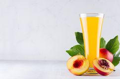 Summer drink - peach juice and red ripe nectarines with leaves and fleshy slice on soft light white wood background. Healthy food backdrop royalty free stock image