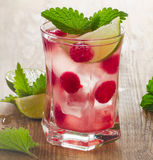 Summer drink with raspberries, lime and ice on a old wooden tabl Royalty Free Stock Photos