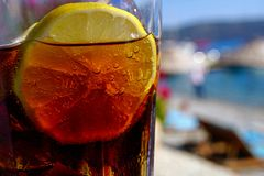 Summer Drink on the Rocks. Refreshing summer drink with sparkling bubbles, ice cubes and lemon siices stock images