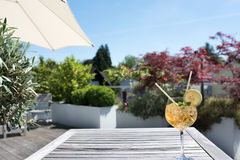 Summer drink on a terrace. Summer drink served on a terrace with sun umbrella and blue sky Royalty Free Stock Photos