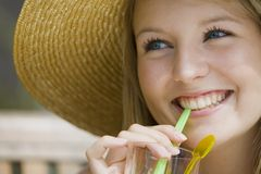 Summer Drinks. A beautiful young blond woman enjoying a tall drink  and wearing a big straw hat Stock Images