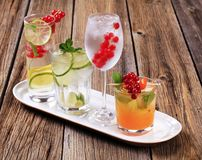 Summer drinks. Glasses of iced drinks garnished with fresh fruit royalty free stock image