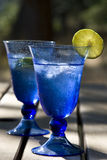 Summer Drinks. A pair of summer drinks in blue glasses, with tinkling ice and lime slices, sit on a picnic table in the afternoon sun Royalty Free Stock Image