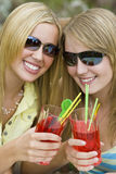 Summer Drinks. Two beautiful young women enjoying drinks in the summer sunshine Stock Image