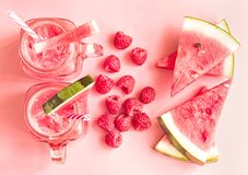 Summer drinks concept. watermelon slices, raspberries and smoothies in mason jar on pink fashion background top view. creative lay stock images