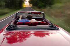 Summer Drive. A middle aged couple snuggle together as they zoom down a county road in a classic red convertible, perhaps on a Sunday drive as they enjoy the Royalty Free Stock Images