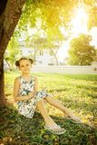 Summer education background: cute little girl sitting on grass and writing in notebook under the tree in warm sun rays. House and. Trees in background Stock Photography