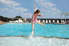 Summer Elation. Girl jumps for joy into the pool as school is over and summer has Royalty Free Stock Photo
