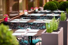 Summer empty open air restaraunt in italian city in Europe. Closeup wineglasses on the table. Summer empty open air restaraunt in italian city in Vienna. Closeup royalty free stock photo