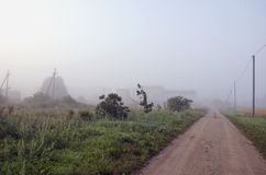 Summer end rural gravel road and morning mist Stock Images