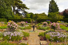 English garden in summer time. Corner of a flagged English garden with stone vase stock photography