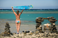 Summer enjoyment. Young woman standing on sea beach with silk shawl Royalty Free Stock Photography