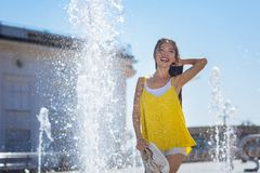 Attractive positive woman standing in the fountain royalty free stock photography