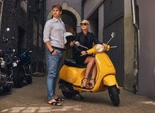 Summer Europe vacation, date, romance. Attractive couple - charming blonde woman wearing black dress sitting on a yellow. Summer Europe vacation, date, romance stock images