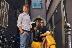 Summer Europe vacation, date, romance. Attractive couple - charming blonde woman wearing black dress sitting on a yellow. Summer Europe vacation, date, romance royalty free stock photography