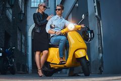 Summer Europe vacation, date, romance. Attractive couple - handsome stylish guy dressed in a white shirt and jeans. Sitting on a yellow classic italian scooter royalty free stock image