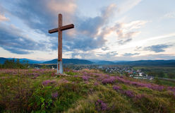 Summer evening country view with wooden cross Stock Images